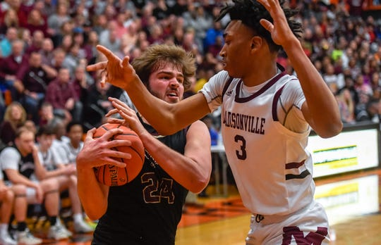 Webster County's Hunter McNaughton (24) drives under the basket under pressure from Madisonville's Kenny White (3) as the Webster County Trojans play the Madisonville Maroons in the Second Region boys championship Tuesday evening at Hopkinsville High School, March 9, 2020.