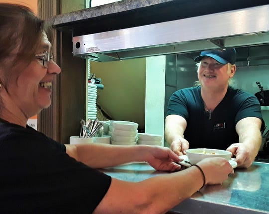 """Gregg Mirabito exhibits strong Irish genes, but has a flare for cooking Italian food. Here he passes one of his """"non-ethnic"""" specialty soups he calls """"Broccoli with an Attitude"""" to his wife Terri at Mirabito's Italian Restaurant in North Liberty."""