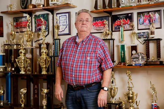 Gene Hurt poses for a photo in front of his wall of trophies of which he figures he has around 200, Tuesday, March 10, 2020 in his Lafayette home.