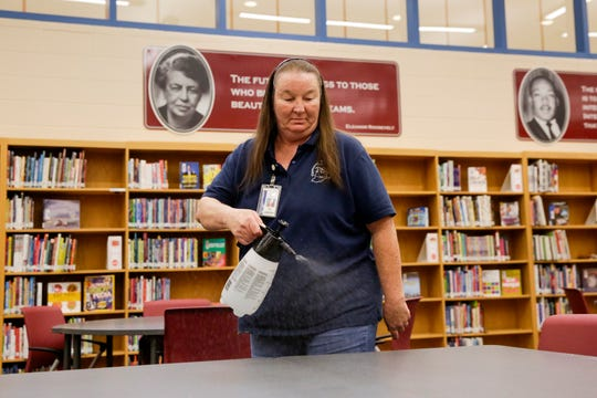Rose Moe, head custodian at Wea Ridge Middle School, sprays a disinfectant solution as she goes about her daily cleaning route inside the school's library, Wednesday, March 11, 2020 in Lafayette.
