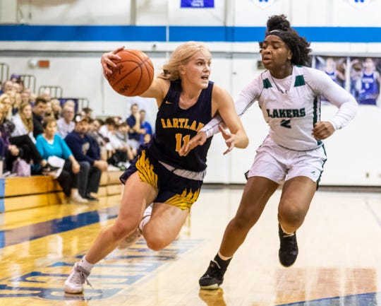 Hartland's Amanda Roach drives against Jade Goodloe in a 61-52 victory over West Bloomfield in a regional semifinal on Tuesday, March 10, 2020 at Walled Lake Western.
