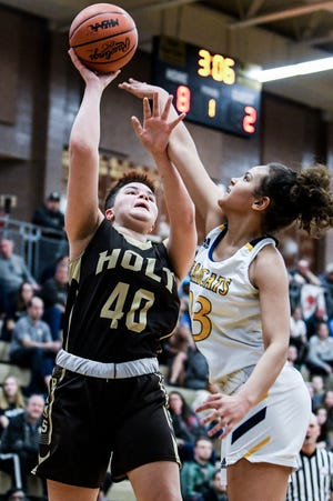 Holt's Jayda Harris, left, scores as Battle Creek Central's Audrey Cook defends during the first quarter on Tuesday, March 10, 2020, at Holt High School.