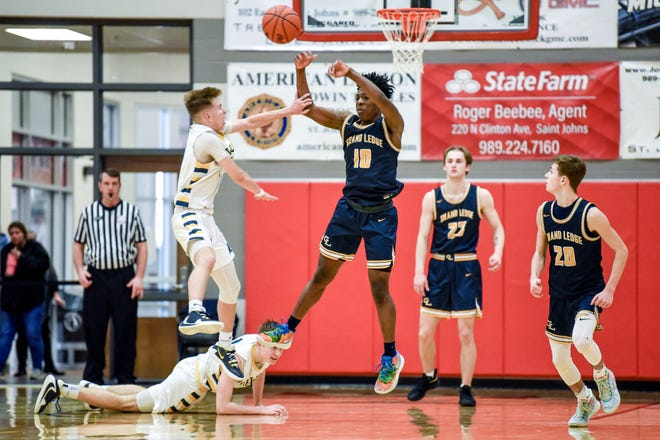 Grand Ledge's Isaiah Bailey, right, passes the ball while being pressured by DeWitt's Caileb Brown during the fourth quarter on Wednesday, March 11, 2020, at St. Johns High School.