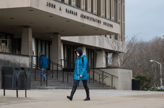 "MSU senior Yue Yang walks past the John Hannah Administration Building on Wednesday, March 11, 2020.  ""The president made a good decision, everyone should just be safe and pay attention,"" she said. ""My parents worry about me but I'll be alright.""  She wears a face mask for her own protection. The university has suspended in-person classes until April 20 and will conduct classes online to minimize the potential spread of coronavirus."