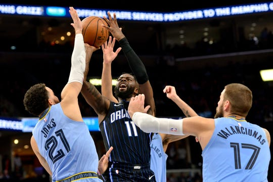 Orlando Magic forward James Ennis III (11) shoots between Memphis Grizzlies guard Tyus Jones (21) and center Jonas Valanciunas (17) during the second half of an NBA basketball game Tuesday, March 10, 2020, in Memphis, Tenn.