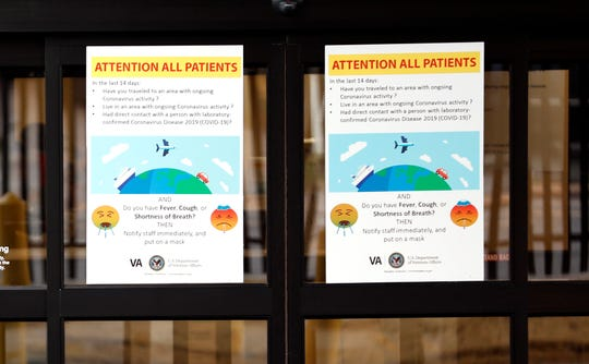 A sign on the doors of the Memphis VA Medical Center warns patients about possible symptoms of coronavirus on Wednesday, March 11, 2020.