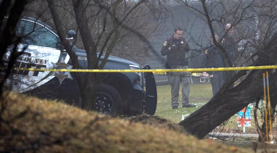 Law enforcement personnel are shown Wednesday at a house on Oak Grove Lane in the Town of Waukesha where two people were fatally stabbed and two others injured Tuesday night. A man was taken into custody.