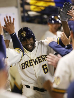 Milwaukee Brewers Lorenzo Cain is congratulated after hitting a lead-off home run during the first inning of their spring training game against the Seattle Mariners.
