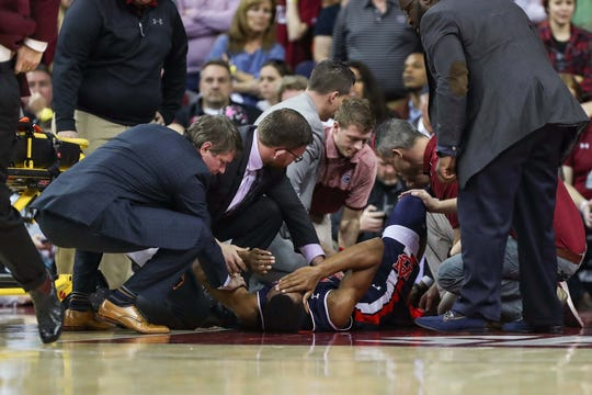 Auburn center forward Anfernee McLemore (24) is surrounded by coaches and EMS suffering an injury against South Carolina at Colonial Life Arena on Feb. 17, 2018, in Columbia, S.C.
