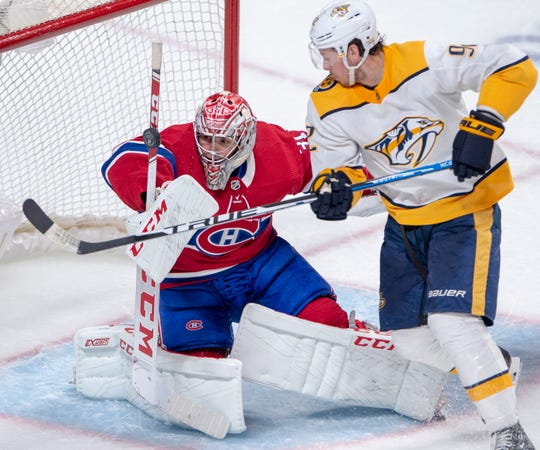 Montreal Canadiens goaltender Carey Price (31) and Nashville Predators centre Ryan Johansen (92) keep their eyes on a loose puck during the second period of an NHL hockey game Tuesday, March 10, 2020, in Montreal.
