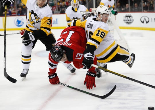 Pittsburgh Penguins center Jared McCann (19) falls over New Jersey Devils center Nico Hischier (13) as they try to get to the puck, lower right, with Penguins defenseman Jack Johnson (3) watching during the second period of an NHL hockey game Tuesday, March 10, 2020, in Newark, N.J.