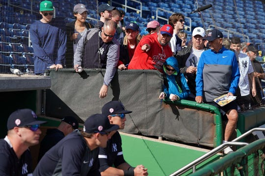 Mar 9, 2020; Clearwater, Florida, USA; Baseball fans try to get autographs from the New York Yankees dugout before their game against the Philadelphia Phillies at Spectrum Field. Teams have had to adjust their autograph policy ahead of spring-training games to try to limit contact between players and fans amid the coronavirus outbreak.