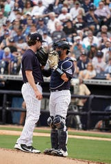 Mar 10, 2020; Tampa, Florida, USA; New York Yankees starting pitcher Gerrit Cole (45) talks with New York Yankees catcher Kyle Higashioka (66) at the mound against the Toronto Blue Jays during the second inning at George M. Steinbrenner Field.