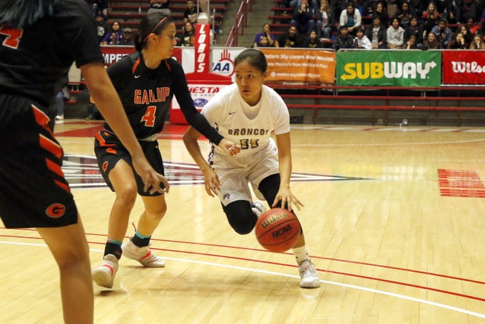 Kirtland Central's Melanie Yazzie drives by a Gallup defender during the first half of their 4A quarterfinals game on March 10, 2020 at The Pit in Albuquerque.