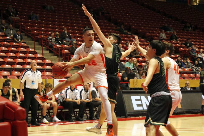 Artesia's Braxton McDonald tries to find a teammate to pass to while he's in the air against Hope Christian on March 11, 2020 at The Pit in Albuquerque. Hope Christian won, 61-26.