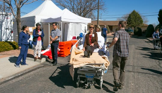 Mock patient Penny Hill is wheeled to a treatment tent during a March 5 coronavirus preparatory drill at San Juan Regional Medical Center in Farmington.