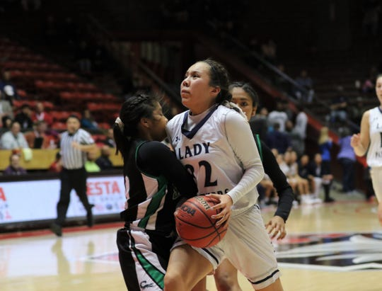 Piedra Vista's Lanae Billy drives toward the basket and collides with Farmington's Jade Henry during Tuesday's NMAA 5A girls basketball state quarterfinals game at Dreamstyle Arena in Albuquerque.