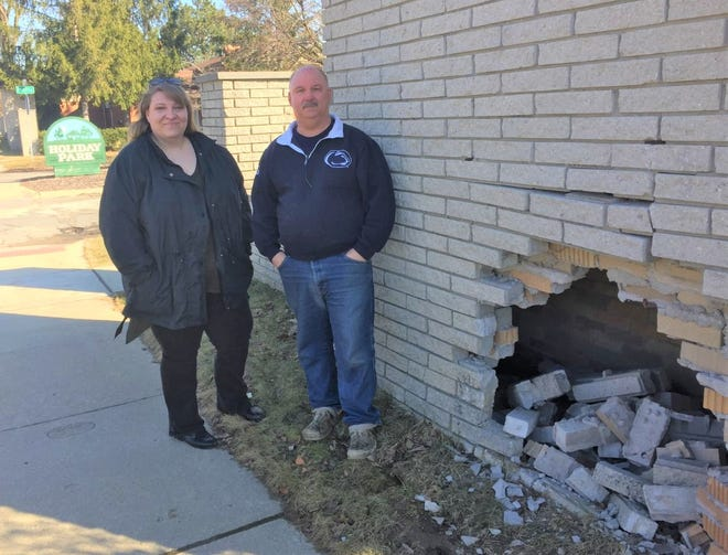 Holiday Park residents Marie Brancheau and Rich Roberts stand next to the damaged wall near the entrance to their subdivision.
