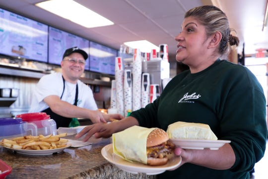 John's Restaurant employees prepare and deliver food on Wednesday, March 11, 2020, in Palm Desert, Calif.