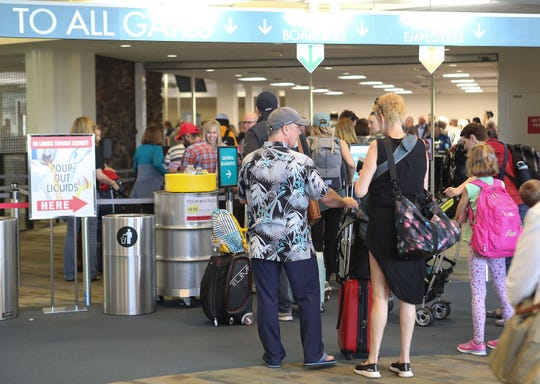 Travelers enter the security checkpoint at Palm Springs International Airport, March 11, 2020.