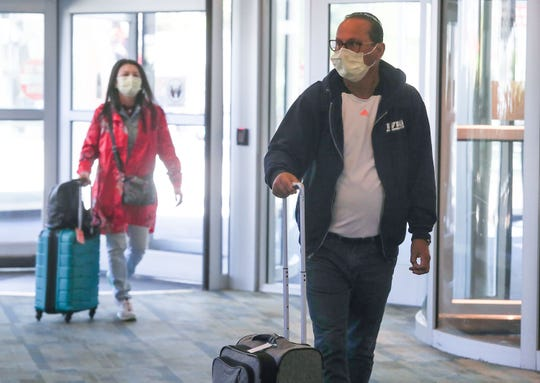 Travelers wearing masks enter Palm Springs International Airport after deplaning from a flight, March 11, 2020.  Nearly all passengers on this day were not wearing masks.