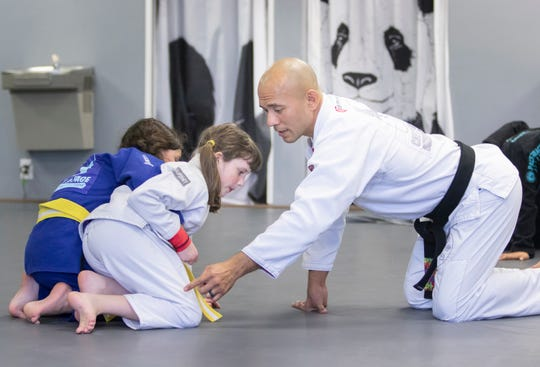Marcello Alcantar gives instructions to Grace Paschal, left, and Ada Andress at Pace Gracie Jiu Jitsu Academy on March 10.