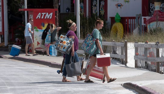 Spring breakers prepare for a day in the sun at Pensacola Beach on Wednesday, March 11, 2020. As the Spring break season arrives along the Gulf Coast, few business owners and visitors are worried about the coronavirus.