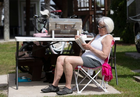 Colorado resident Marne Engelking relaxes in the sun at the Pensacola Beach RV Resort on Wednesday, March 11, 2020. Engelking and her husband Steve, are not worried about the coronavirus because they are not staying in hotels or other lodgings while traveling the country in their RV.