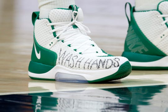 Mar 10, 2020; Indianapolis, Indiana, USA; Boston Celtics center Enes Canter (11) wears a message on his shoes for fans to wash their hands as a precaution for coronavirus CoVid 19 during a game against the Indiana Pacers at Bankers Life Fieldhouse. Mandatory Credit: Brian Spurlock-USA TODAY Sports