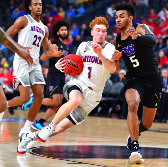 Mar 14, 2020; Las Vegas, Nevada, USA;Arizona Wildcats guard Nico Mannion (1) drives against Washington Huskies guard Jamal Bey (5) during the first half at T-Mobile Arena. Mandatory Credit: Stephen R. Sylvanie-USA TODAY Sports