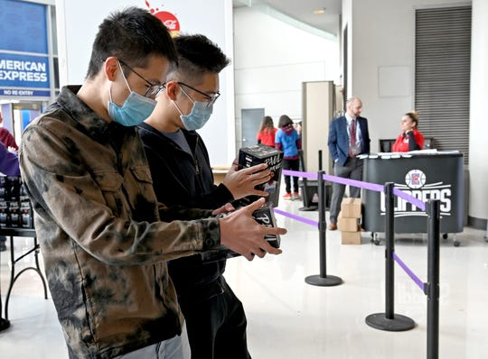 Fans wear masks as they receive a Paul George bobblehead when they enter Staples Center for a game between the Los Angeles Clippers and the Philadelphia 76ers. Management has placed sanitizing stations throughout the building due to the recent coronavirus situation.
