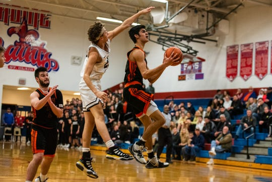 Lutheran North's Gary Glaser III (left) reaches over Marine City's Jack Kammer to block a shot during the MHSAA Division 2 district semifinal Wednesday, March 11, 2020, at St. Clair High School.