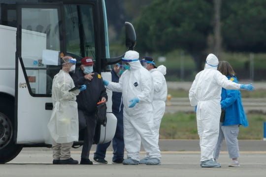 Passengers from the Grand Princess, a cruise ship carrying multiple people who have tested positive for COVID-19, exit a bus before boarding a chartered plane in Oakland, Calif., Tuesday, March 10, 2020. The passengers on the flight are going to San Antonio to be quarantined at Lackland Air Force Base. (AP Photo/Jeff Chiu)