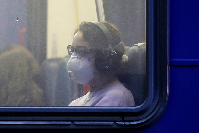 In this March 6, 2020 photo, a woman wears a mask as she rides a bus in downtown Seattle during an evening commute. Starting Monday, the Regional Transportation Commission of Washoe County will offer free RIDE, FlexRIDE and ACCESS trips to locations that offer the COVID-19 vaccine.