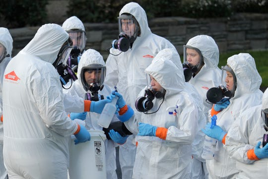 Workers from a Servpro disaster recovery team wearing protective suits and respirators are given supplies as they line up before entering the Life Care Center in Kirkland, Wash., to begin cleaning and disinfecting the facility, Wednesday, March 11, 2020. The nursing home is at the center of the coronavirus outbreak in Washington state.