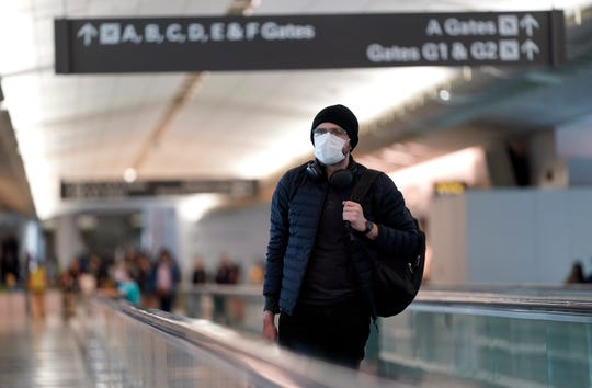 An airline passenger wearing a mask making his way through an airport during the coronavirus pandemic.