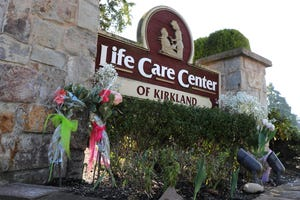 Flowers left next to the sign that marks the entrance to the parking lot of the Life Care Center in Kirkland, Wash. are shown March 9, 2020, near Seattle. The nursing home is at the center of the outbreak of the COVID-19 coronavirus in Washington state.