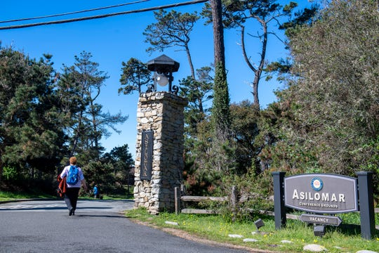 A woman is seen walking through the Asilomar Conference Grounds entrance March 11, 2020.