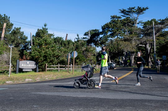 A couple jogs together near the Asilomar Conference Grounds March 11, 2020.