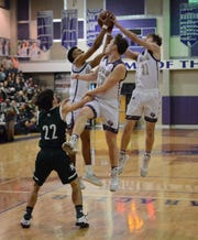 San Saba High School's Risien Shahan (12) watches his teammates Sean O'Keefe (left) and Logan Glover (21) try to haul in a rebound against Normangee during the Region IV-2A championship game Saturday, March 8, 2020, at the Snake PIt at San Marcos High School.