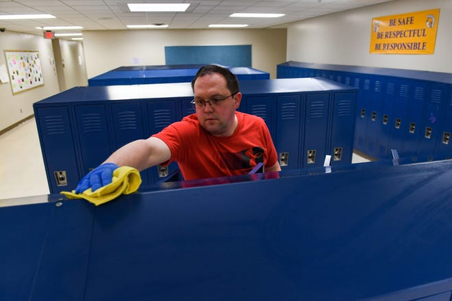 Craig Kuca sanitizes locker clusters in the halls of West Central High School on Wednesday, March 11, in Hartford.