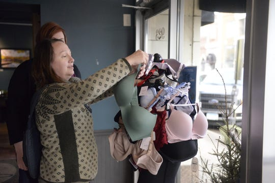 Jessica Gauerke hangs a bra she brought as a donation for a Lift Up the Ladies event onto the mannequin at Jules' Bistro Monday, March 9, 2020.