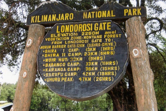 A sign at the beginning of the Lemosho route up Mount Kilimanjaro lists the altitudes and the hours of hiking it takes to reach each camp, in early 2020.