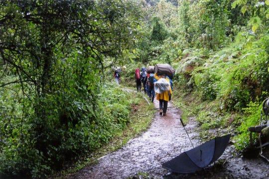 Porters hike through muddy trails as rain pours down on the Lemosho route up Mount Kilimanjaro in Tanzania, 2020.