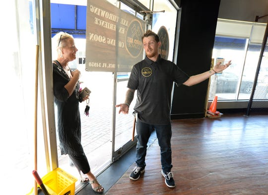 """Janet Roessler (left), a new Fort Pierce resident, inquiries about the new business Hard Axe Lounge from its owner and operator Julian Hewatt at the front door on Wednesday, March 11, 2020, at 200 North 2nd St. in downtown Fort Pierce. Hewatt is still preparing the venue for opening sometime in the coming weeks. """"I wanted to work for myself and I wanted to bring a new exciting idea to downtown Fort Pierce,"""" Hewatt said. """"I went and did it (ax throwing) in Orlando, and thought it was genius, exciting and fun. And I love this city. I thought if we were going to do it we need to do it here."""""""