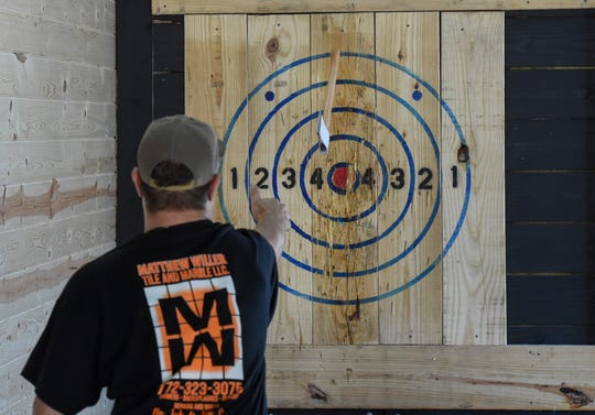 """Matt Willer, a friend of Julian Hewatt, tries his skill at ax throwing, aiming for the target while taking a break from helping Hewatt, owner and operator of Hard Axe Lounge, prepare for opening  Wednesday, March 11, 2020, in downtown Fort Pierce. """"It's something new, it's a blast,"""" Hewatt said about the sport. """"The first time you stick a bullseye you're addicted."""""""