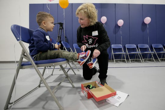 Volunteer Donna Neessen helps Brandon Macias try on his new shoes, donated to Thomas Manor Elementary School students by the Braden Aboud Memorial Foundation on Wednesday, March 11, 2020.