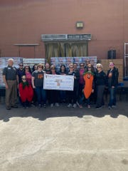 Junior League and Food Bank representatives receive check for $4k from McEntire Heavy Haul as part of their yearly Food Fight food drive.
