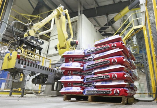 Heritage Cooperative Inc. has agreed to purchase the feed, grain, trucking and agronomy assets of Hanby Farms in Nashport, including the company's Performance Feed brand, seen being loaded onto a pallet by one of the Nashport company's robotic palletizers.