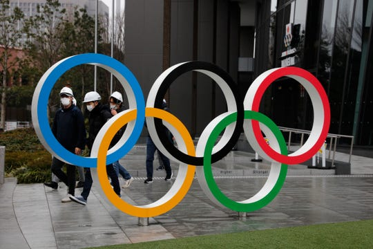 People wearing masks walk past the Olympic rings near the New National Stadium in Tokyo.